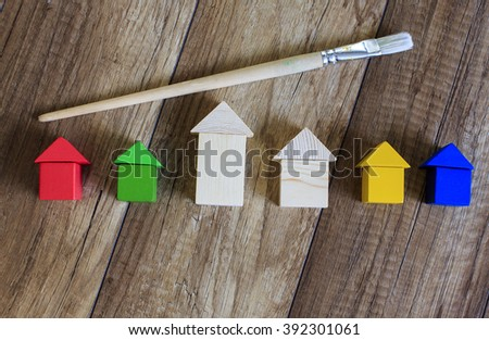 concept of painting works. wooden houses of the toy bricks and brush symbolizes the work of a painter. top view, flat lay