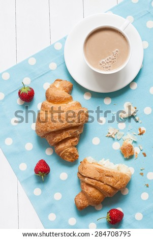 Concept of perfect breakfast or lunch, croissasnt traditional pastry dessert with a cup of coffee and fresh strawberry on provence style background. Natural light and rustic style. - stock photo