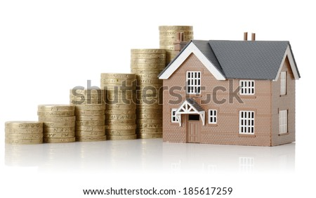 Concept of property value, house and coins isolated on a white background - stock photo