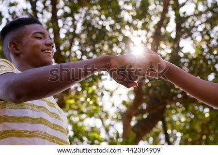 Concept of racism. Two young multiethnic teens meeting together in park and joining hands. - stock photo