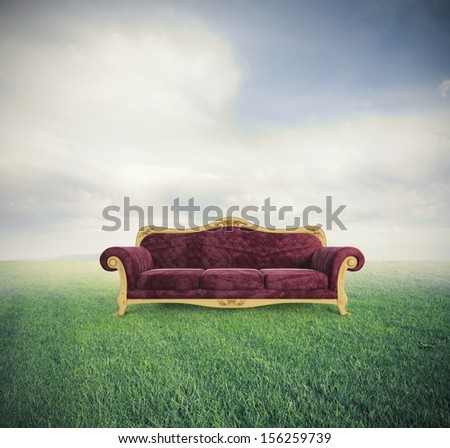 Concept of relax and comfort with a velvet red sofa in a green field - stock photo