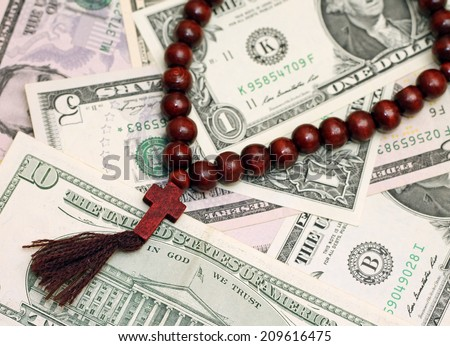 Concept of religion as business - rosary beads with dollars - stock photo