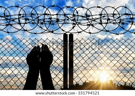 Concept of religion. Silhouette of hands facing the sky against a background of a fence with barbed wire and the city in the distance