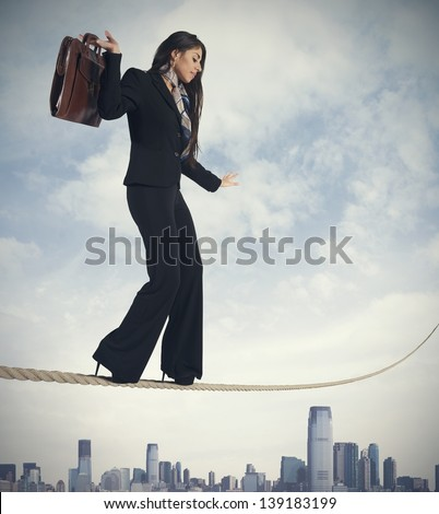 Concept of risk in business with businesswoman on the rope - stock photo