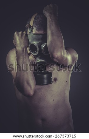 concept of risk of contamination, naked man with gas mask - stock photo