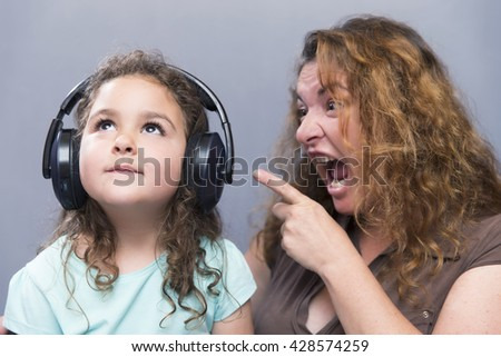 Concept of screaming mother at kid listening to music in headphones - stock photo