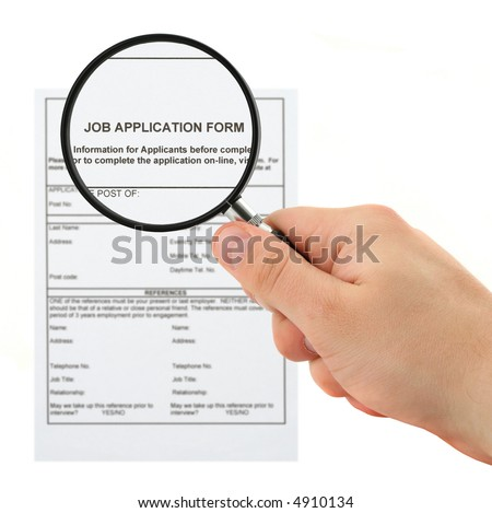 concept of searching for personnel - hand with magnifying glass and job application form - stock photo
