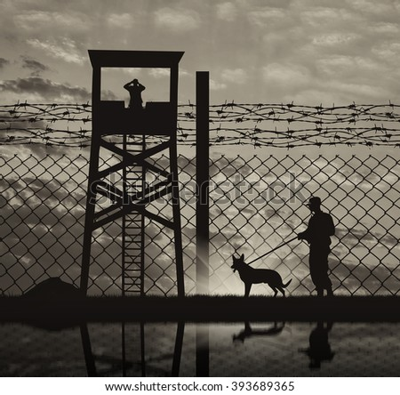 Concept of security. Silhouette of a lookout tower and a guard with a dog on the background of the fence with barbed wire and reflection