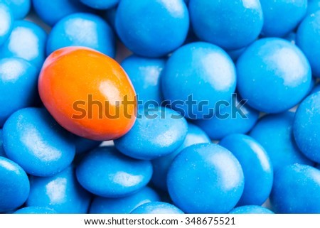 Concept of selective focus on orange chocolate candy against heaps of blue candies in background