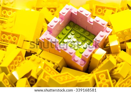 Concept of selective focus on secured and protected green area within wall constructed using building blocks, against heaps of yellow bricks - stock photo
