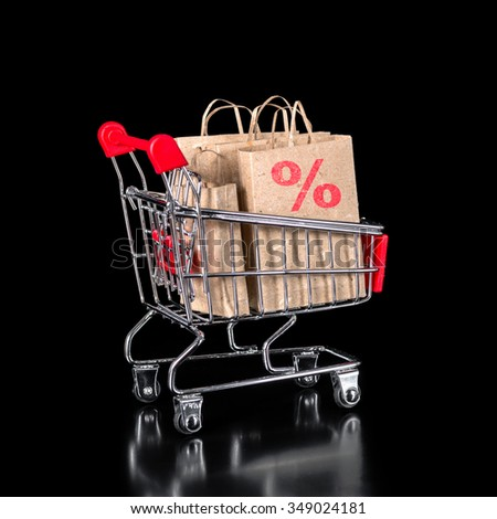 concept of shopping trolley with paper bags is isolated on black background - stock photo