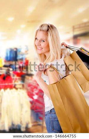 Concept of shopping with blond girl carrying bags - stock photo