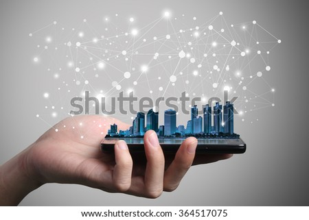 Concept of smart phone communication network. Double layers view of city scape and indoor hand image isolated on gray background. - stock photo