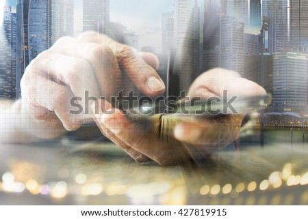 Concept of smart phone connection to urban life. Double layers view of city scape and indoor hand image. - stock photo