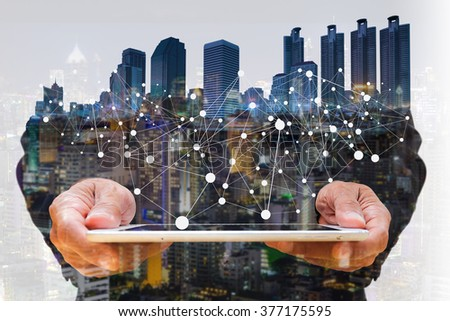 Concept of smart phone or tablet connecting network to urban life. Double layers view of city scape and indoor hand image.