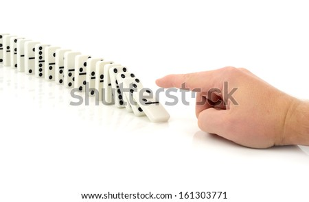 Concept of starting a process or chain reaction of events, finger pushing a domino isolated on a white background - stock photo