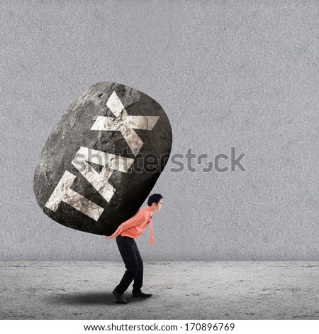 Concept of stress of a businessman carrying a big rock of TAX - stock photo