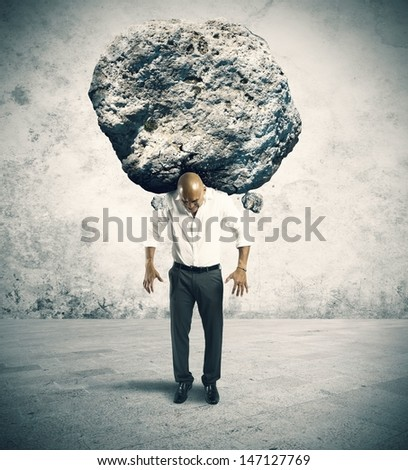 Concept of stress of a businessman with a big rock - stock photo