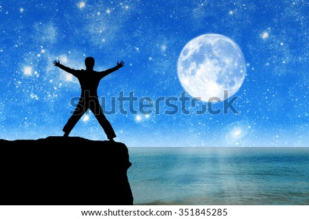Concept of success. Silhouette of a happy man on the mountain top on background of the sea in the moonlight night - stock photo