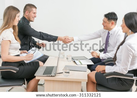 concept of successful business - meeting with two men shaking hands and there are a two business women at foreground sitting at office