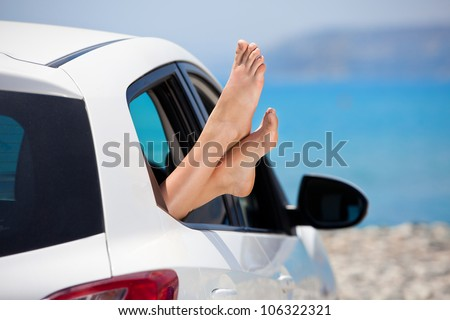 Concept of summer car trip vacation . Woman legs out the window in car at background of sea water. Conceptual travel ,freedom and holidays image. - stock photo