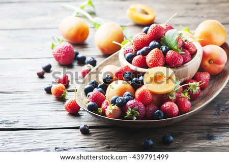 Concept of summer healthy food with strawberry, blueberry and apricot, selective focus