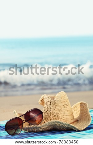 Concept of summer holidays with straw hat and sunglasses on sandy beach - stock photo