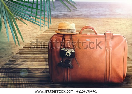 Concept of summer traveling with old suitcase on blur beach background. - stock photo