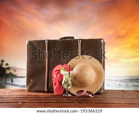 Concept of summer travelling with old suitcase and accessories. Blur beach on background - stock photo