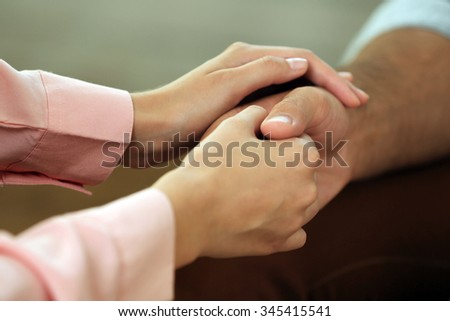 Concept of support - man and woman holding hands in the light room - stock photo