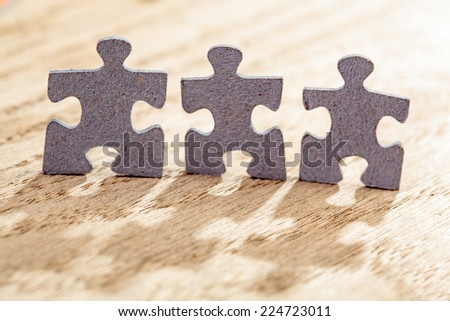 Concept of teamwork: Three jigsaw puzzle pieces on a table. Shallow depth of field