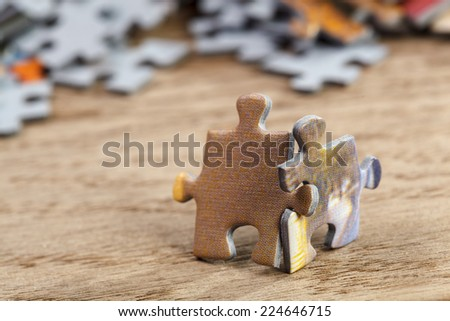 Concept of teamwork: Two jigsaw puzzle pieces on a table joint together. Shallow depth of field - stock photo