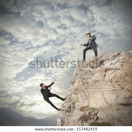 Concept of teamwork with climbing businessman - stock photo