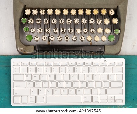Concept of technology progress - old typewriter and new computer keyboard on wooden background - stock photo