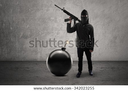 Concept of terrorism. Male rebel wearing dark clothes and mask, carrying rifle with bomb - stock photo