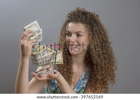 Concept of the cost of living a smiling woman holding supermarket trolley full of cash