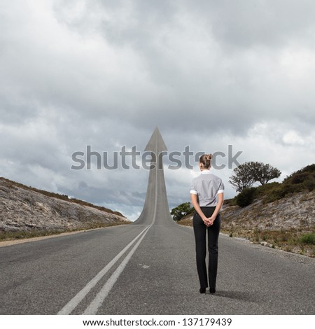 Concept of the road to success with a businesswoman standing on the road - stock photo
