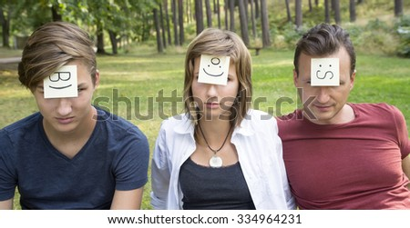 Concept of thoughts and emotions. On the foreheads shows (drawn) worry, angel and cool icons on yellow stickers. Man, girl and boy are sitting on the green grass in nature sunny day. - stock photo