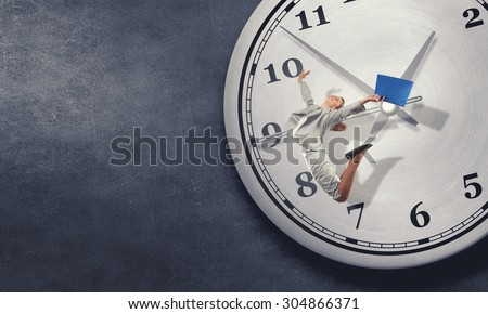 Concept of time with jumping businesswoman over big alarm clock - stock photo