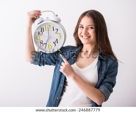 Concept of time. Young smiling woman is holding a watch. - stock photo