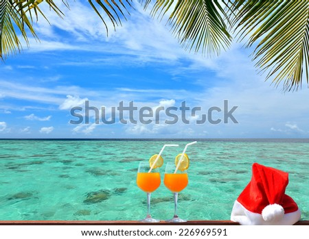 Concept of tropical christmas holidays -- Two tropical fresh juices and red santa hat near the beautiful tropical green lagoon - stock photo