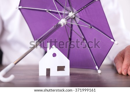 Concept of umbrella protecting a house - stock photo