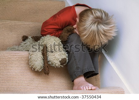 Concept of upset child with his toy dog. - stock photo