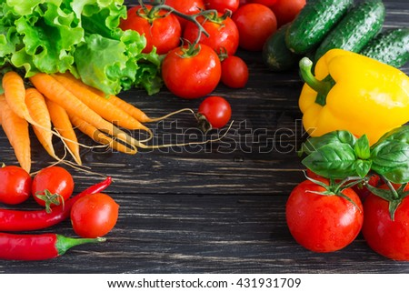 Concept of vegetarian food with  tomatoes on vine, yellow paprika, red chilli, carrots, cucumbers and green basil on black rustic wooden background - stock photo