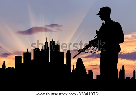 Concept of war and crisis. Silhouette of military weapons against the evening city
