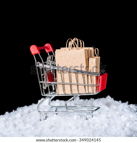 Concept of winter sale. Shopping cart with paper bags in snow is isolated on black background, closeup - stock photo