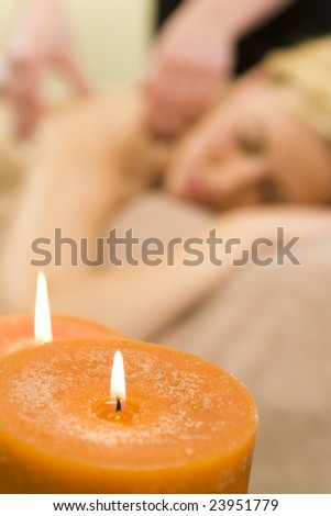 Concept or background shot of a young woman relaxing at a health spa while having a massage focus is on two candles in the foreground
