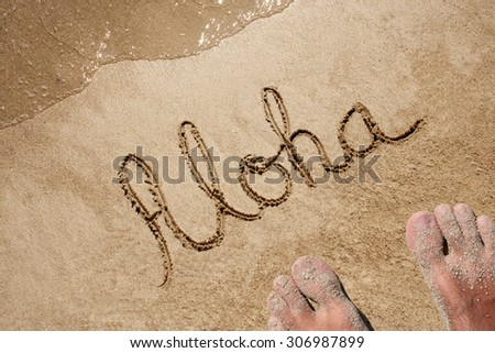 Concept or conceptual Aloha text handwritten in sand on a beach with feet in an exotic island for tropical, summer, sea, ocean, calendar, travel, holiday, sunny, tourism, resort, time or relaxet - stock photo