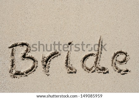 Concept or conceptual hand made or handwritten bride text in sand on a beach in an exotic island, metaphor to summer,ocean,sea,travel,vacation,tourism,tropical,happy,message,paradise wedding or couple
