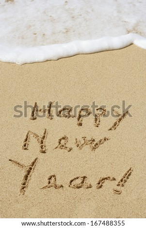 Concept or conceptual hand made or handwritten Happy new year text in sand on a beach in an exotic island